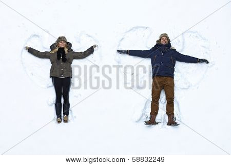 Young couple lying in fresh snow, making snow angels having fun.