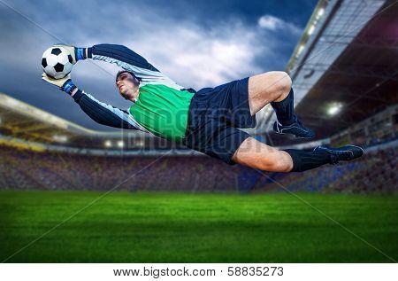 Football goalkeeper in action on field of stadium