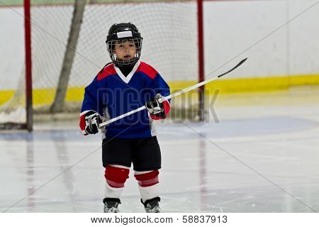 Little Boy Playing Ice Hockey In An Arena