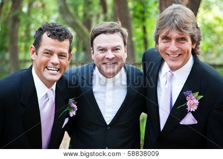 Minister posing with a handsome gay wedding couple he has just married.  *focus is on the minister.
