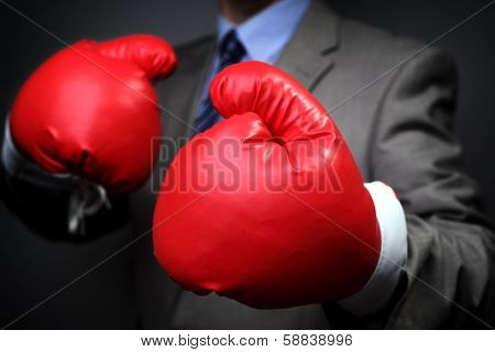 Tough competitive business concept businessman wearing boxing gloves