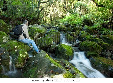 trekker resting next to a river torrent