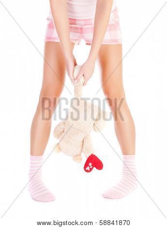 Conceptual image of one-sided love, front view of woman wearing pink pajamas, girl holding bear in hands, break up, heartbroken female, first unhappy love, sadness and loneliness concept
