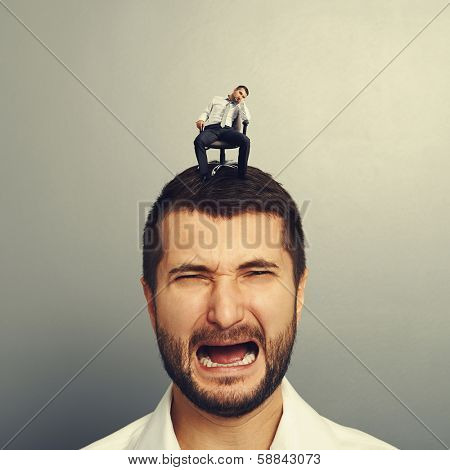 portrait of sad screaming man with small bored man on the head