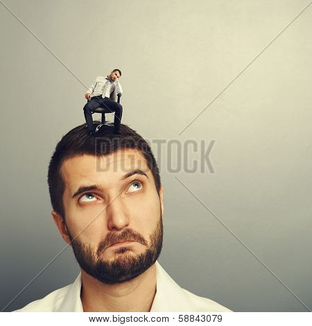 amazed young man looking at bored man over dark background