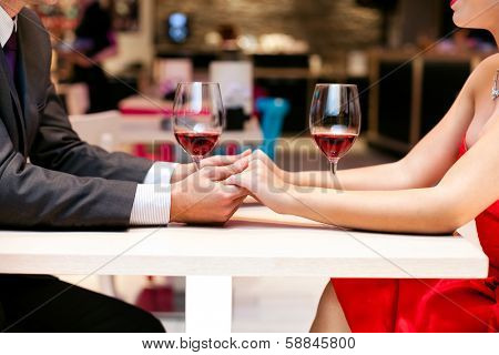 Couple in love holding hands together on table in restaurant, close up