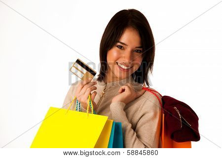 Attractive asian caucasian woman with shopping bags and credit card in her hands isolated over white