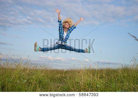 Professional gymnast woman jump in green grass field