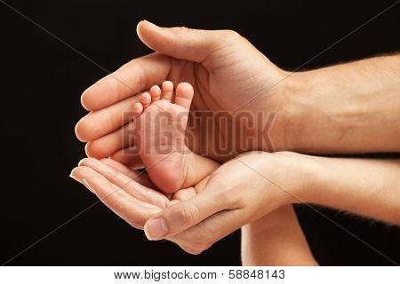 Newborn baby foot in parents hands