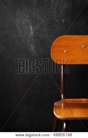 Wooden school chair against blackboard