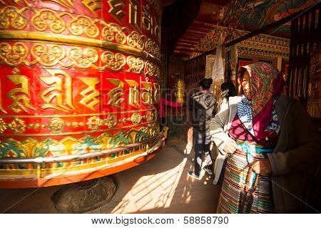 KATHMANDU, NEPAL - DEC 20: Unidentified pilgrimage near spinning Big Tibetan Buddhist prayer wheel at Boudhanath Stupa, Dec 20, 2013 in Kathmandu, Nepal.