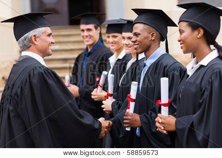 senior university professor handshaking with young graduates