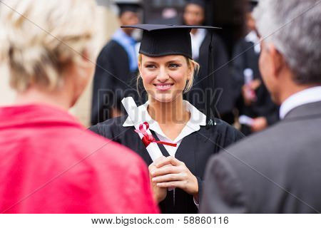 middle aged couple attending daughter's university graduation ceremony