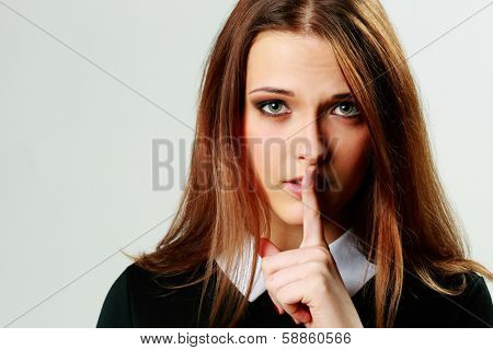 Closeup portrait of a young woman with silence sign isolated on gray background