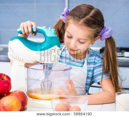 little girl with a mixer whisk the eggs in the kitchen at home
