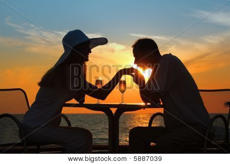 Man Kisses  Hand To  Woman On Sunset Behind  Table Outside