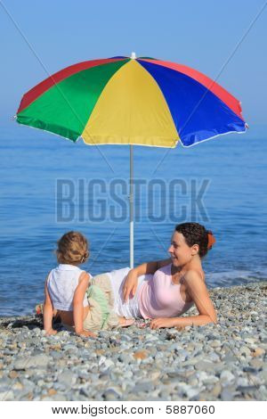 Mother With Child Under A Multi Colored Umbrella On Pebble Beach