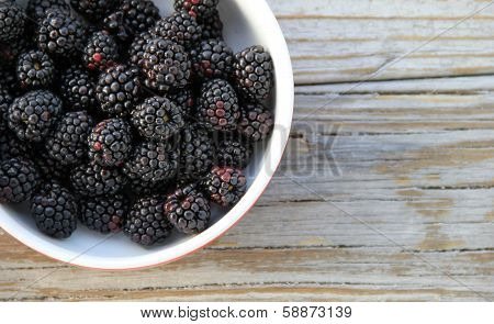 Bowl of blackberries on gray wood