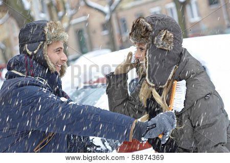 Young loving couple having fun in snowfall, brushing off car, throwing snowball.