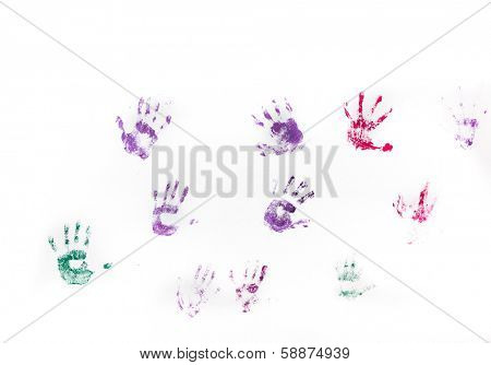 Different children's hand prints on white wall.