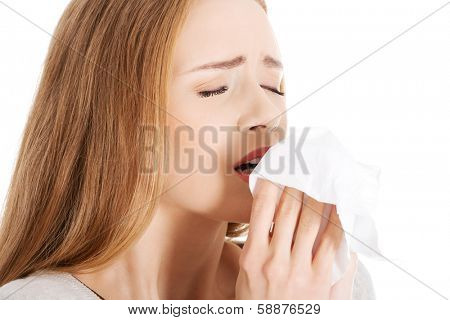 Beautiful woman sneezing, holding a tissue. Isolated on white.