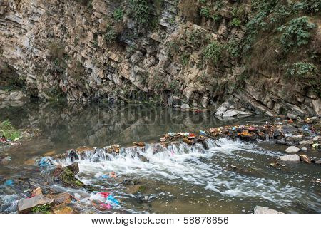 Environmental pollution in the Himalayas. Garbage in the water of river.