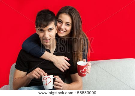 Portrait Of Cute Couple With Mugs On Sofa.