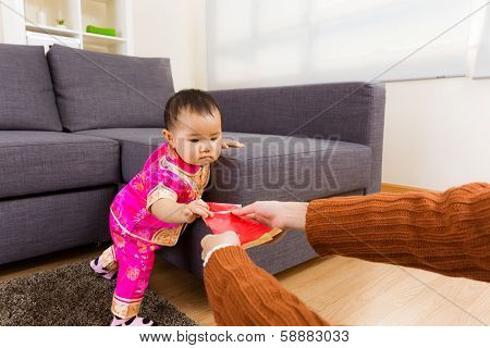 Chinese baby taking red pocket from adult