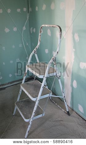 Step stool and wall daubed with plaster