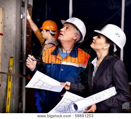 Business woman in builder helmet indoor.
