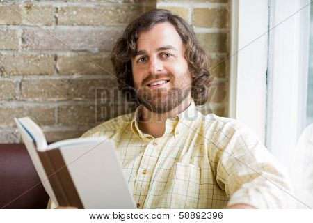 Portrait of mid adult man with book sitting by window in coffeeshop
