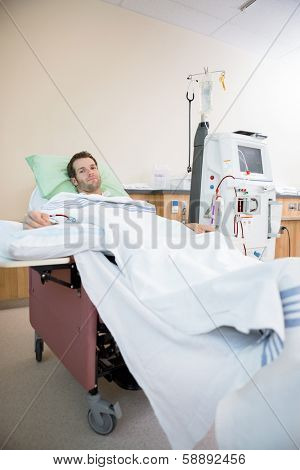 Portrait of young male patient receiving renal dialysis in hospital room