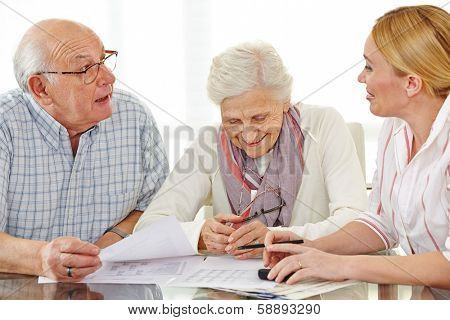 Couple of senior citizens talking to financial consultant about their pension