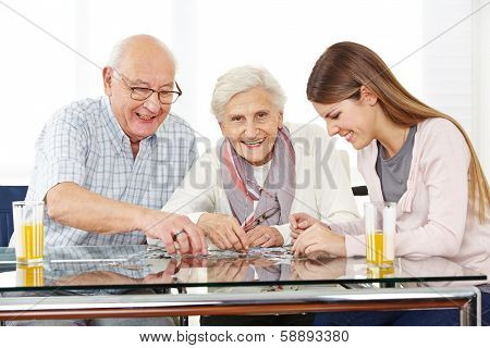 Couple senior citizens playing with a jigsaw puzzle with her granddaughter