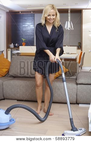 Pretty blonde girl in dressing gown using vacuum cleaner at home, smiling.