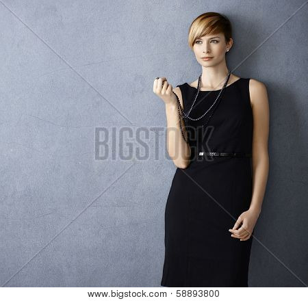 Attractive young woman wearing black dress and pearl necklace on grey background