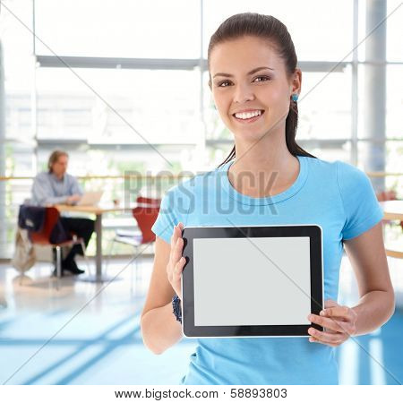 Portrait of young woman holding tablet computer, smiling, looking at camera.