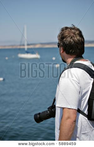 Photographer Looking At The Sea And Boat.