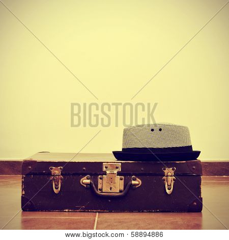 picture of a hat on an old suitcase, with a retro effect