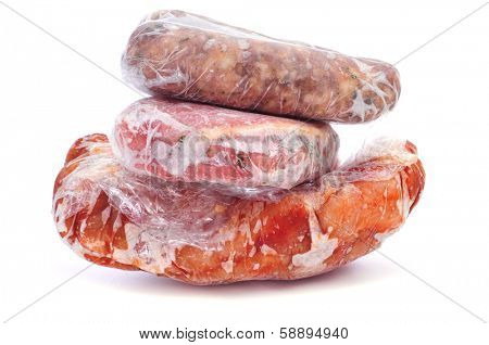 frozen sausages and different meat wrapped in plastic on a white background