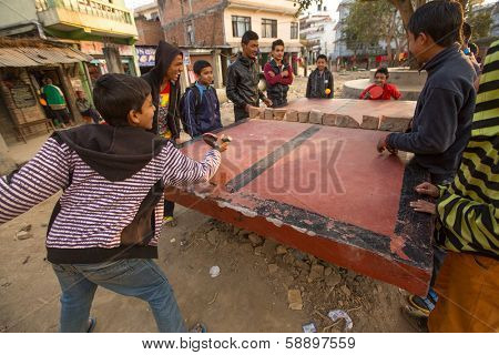 KATHMANDU, NEPAL - DEC 20: Unidentified teenagers from poor families play in table tennis in the slums, Dec 20, 2013 in Kathmandu, Nepal. Caste of untouchables in Nepal, is about 7 % of population.