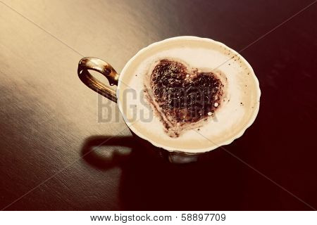 Cup of coffee with chocolate heart shape on milk foam. Romantic morning light. Vintage