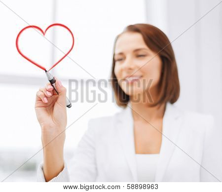 office, business and technology concept - businesswoman drawing heart in the air with marker