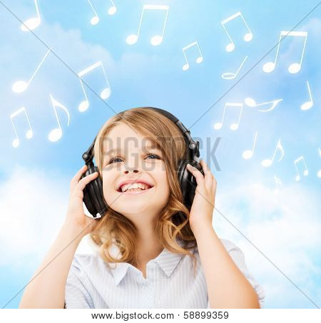 home, leisure, new technology and music concept - smiling little girl with headphones over blue sky background and music notes