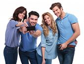 picture of two women taking cell phone  - two couples of young people taking their picture with a phone on white background - JPG
