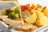 stock photo of christmas dinner  - Pouring gravy on a festive turkey meal with roast yams roast parsnips boiled potatoes and stuffing - JPG