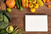 picture of eatables  - studio photography of open blank ringbound notebook surrounded by a fresh vegetables on old wooden table - JPG