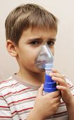 stock photo of bronchus  - Little boy having inhalation for easing cough - JPG