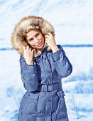 Attractive young lady outdoors in wintertime, wearing stylish winter clothes, warm coat with furry hood, fashionable winter look concept poster