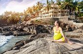stock photo of guest-house  - Yoga by woman in yellow costume on the stone nearby ocean and tropical resort in Kovalam Kerala India - JPG